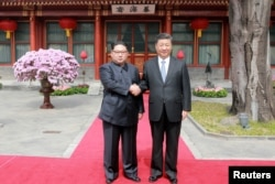 FILE - North Korean leader Kim Jong Un shakes hands with Chinese President Xi Jinping in Beijing, as he paid an unofficial visit to China, in this undated photo released by North Korea's Korean Central News Agency in Pyongyang, March 28, 2018.