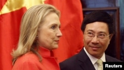 FILE - In this photo from July 2012, Vietnam's Foreign Minister Pham Binh Minh and then-U.S. Secretary of State Hillary Clinton prepare to walk to the meeting room at the Government Guest House in Hanoi.