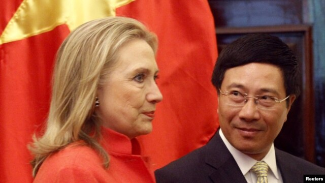 Vietnam's Foreign Minister Pham Binh Minh (R) looks at U.S. Secretary of State Hillary Clinton as they walk to the meeting room at the Government Guest House in Hanoi, July 10, 2012.