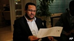 Libyan dissident Abdel Hakim Belhaj holds a letter of apology he received from British Prime Minister Theresa May, following a news conference in Istanbul, Turkey, May 10, 2018.