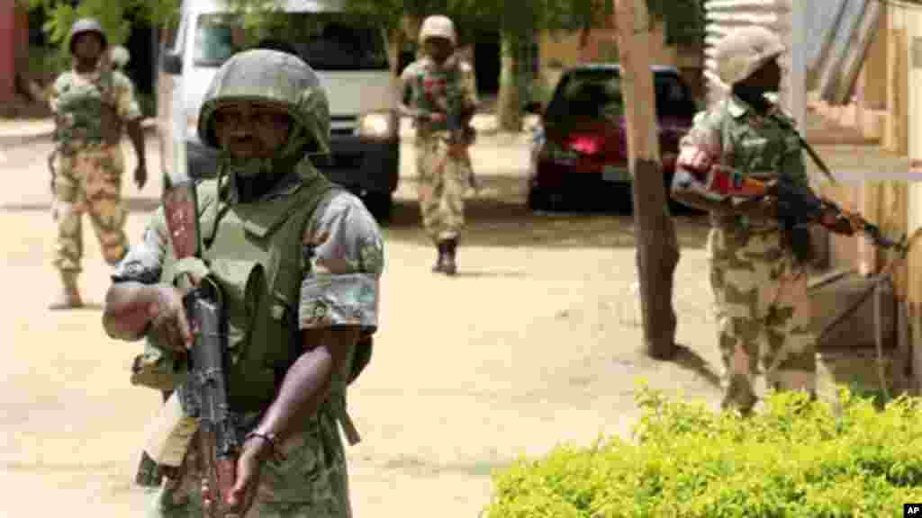 Soldiers stand guard at the offices of the state-run Nigerian Television Authority in Maiduguri, Nigeria.