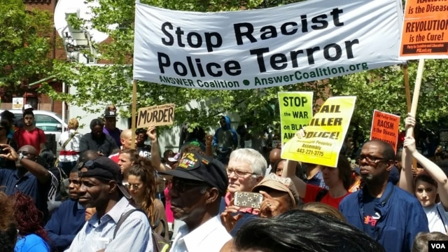 "People march under a banner that reads ""Stop Racist Police Terror,"" Baltimore, Maryland, May 2, 2015. (R. Muntu/VOA)"
