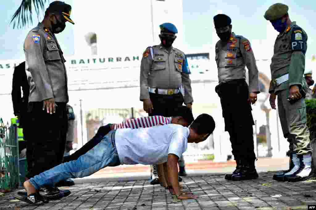 Men perform push-ups as punishment for not wearing face masks amid the Covid-19 coronavirus pandemic in Banda Aceh, Indonesia.