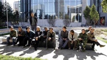 中国农民工在北京一家商店附近休息(2008年10月)