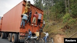 FILE - Young people on bicycles hang to the back of a truck July 19, 2015, outside the capital Bujumbura, Burundi.