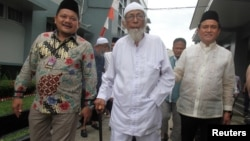 Abu Bakar Bashir, center, the alleged mastermind of the 2002 Bali bombings, walks as he is visited by Yusril Ihza Mahendra, right, who is the lawyer of Indonesia's presidential candidate Joko Widodo, at Gunung Sindur prison in Bogor, Indonesia, Jan. 18, 2019.