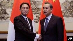 Menteri Luar Negeri Jepang Fumio Kishida (kiri) berjabat tangan dengan Menteri Luar Negeri China Wang Yi dalam pertemuan di Beijing (30/4). (AP/Jason Lee)