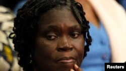 Ivory Coast's former first lady Simone Gbagbo (L) looks on as she attends the first day of her trial at the Palace of Justice in Abidjan December 26, 2014. Simone Gbagbo went on trial in Abidjan on Friday for her alleged role in stealing an election her h