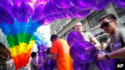 Kajsa Westman, second from right, of Stockholm, Sweden, and Victor Ng, right, of Seattle, tie balloons to a banner in preparation for the annual Gay Pride parade, file photo.