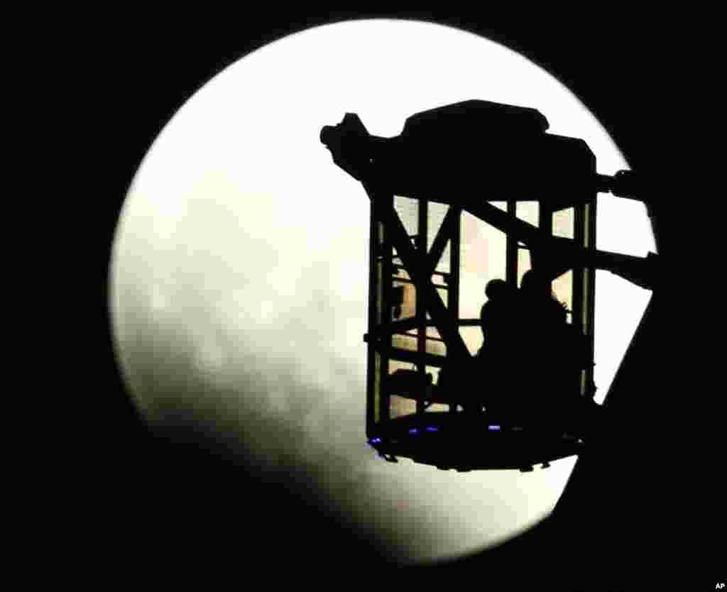 A couple on a Ferris wheel observes the Earth's shadow crossing the moon during a total lunar eclipse in Tokyo, Japan, Oct. 8, 2014.