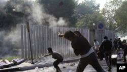 Một người biểu tình phản đối chính phủ ném trả lựu đạn cay về phía cảnh sát Thái Lan, 26/12/13