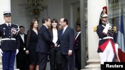 Mantan Presiden Nicolas Sarkozy (dua dari kiri) berjabat tangan dengan presiden baru Francois Hollande (kanan) di akhir upacara pelantikan presiden Perancis di Istana Elysee di Paris (15/5). Nampak mantan ibu negara Carla-Bruni Sarkozy (dua dari kanan) da