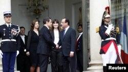 Mantan Presiden Nicolas Sarkozy (dua dari kiri) berjabat tangan dengan presiden baru Francois Hollande (kanan) di akhir upacara pelantikan presiden Perancis di Istana Elysee di Paris (15/5).