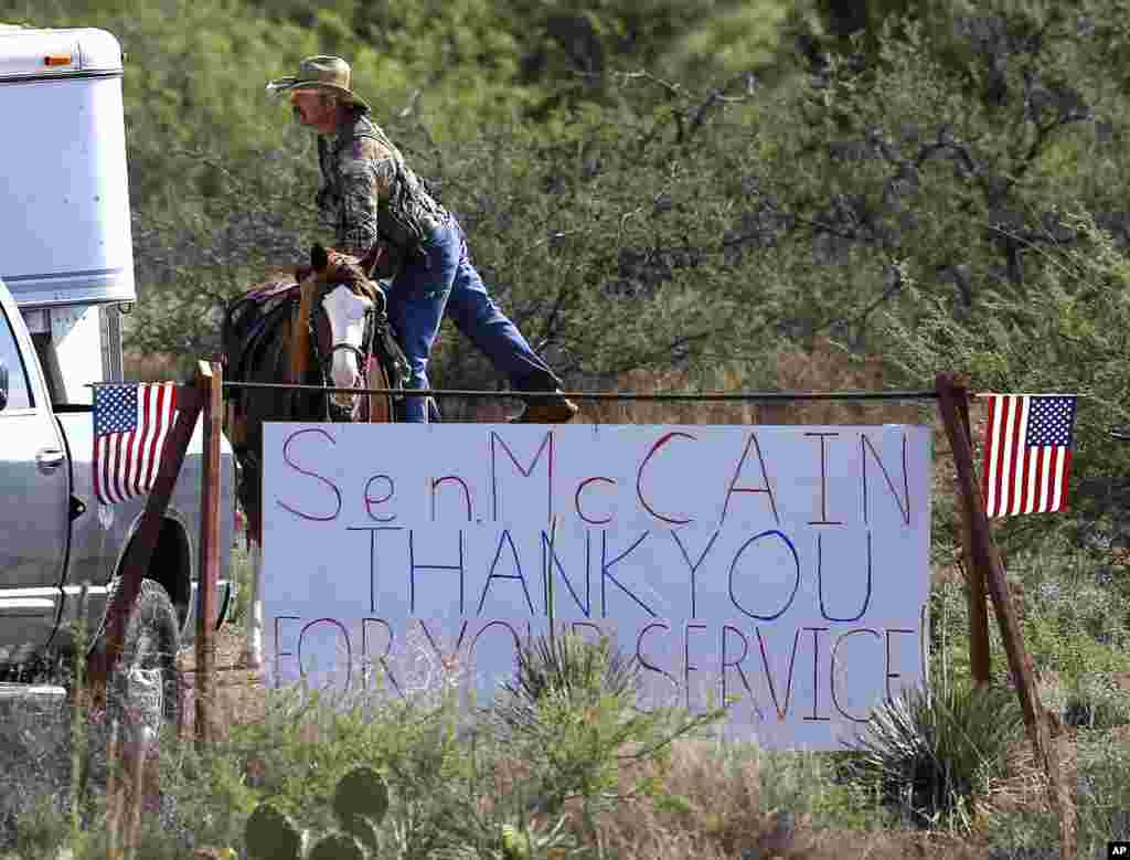 A rancher gets off his horse at the entrance to the McCain ranch complex, Aug. 25, 2018, in Cornville, Ariz.