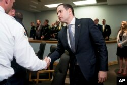 FILE - Sen. Marco Rubio, R-Fla., greets officers as he arrives for a meeting between President Donald Trump and law enforcement officers at Broward County Sheriff's Office in Pompano Beach, Fla., Feb. 16, 2018.