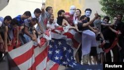 Waandamanaji wanachana bendera ya Marekani waloivuta kutoka ubalozi wa Marekani Cairo. Sept11, 2012.