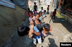 Children from the Rohingya community play outside their shacks in a camp in New Delhi, Oct. 4, 2018.