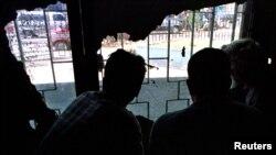 En la foto de archivo tres ciudadanos ecuatorianos miran a través de una ventana dentro de un centro de detención de inmigrantes en la Ciudad de Guatemala.