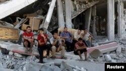 Người dân Palestine ngồi trên đống đổ nát từ những ngôi nhà bị phá hủy trong khu vực Shejaia ở thành phố Gaza 6/8/2014.