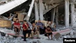 Dân Palestine ngồi trên đống đổ nát của nhà cửa bị phá hủy sau các vụ không kích của Israel vào thành phố Gaza, ngày 8/6/2014.