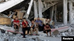 Palestinians sit amid the rubble of homes destroyed in the Shejaia neighborhood of Gaza City on Aug. 6, 2014.