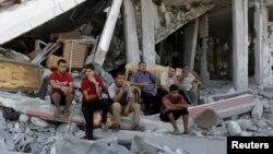 Warga Palestina duduk di antara reruntuhan gedung di distrik Shejaia, Gaza (6/8). Israel setuju untuk memperpanjang gencatan senjata dengan Hamas.