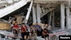 8月6日巴勒斯坦人坐在加沙被毁坏的住房废墟中