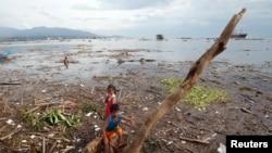 17일 태풍 '람마순'이 필리핀 마닐라 남부를 휩쓸고 지나간 후 쓰러진 나무 주변에서 아이들이 뛰놀고 있다.