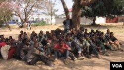 Illegal Ethiopian immigrants await trial outside the Karonga Court, Malawi, Sept. 24, 2014. (Tiwonge Kumwenda/VOA)