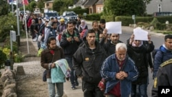FILE - Middle Eastern migrants, who came from Germany by ferry and train Sunday night, and are walking from Rodby in southern Denmark toward Sweden.