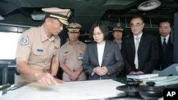 Presiden Tsai Ing-wen (tengah), mengkaji bagan-bagan kelautan di atas kapal Angkatan Laut Taiwan di kota pelabuhan Khaohsiung, Taiwan, Juli 2016.