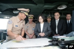 In this image taken and made available by the Taiwan Presidential Office, Taiwan's President Tsai Ing-wen (center right) reviews nautical charts aboard a Taiwan Navy ship before it sets out to patrol in the South China Sea.