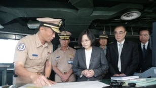 FILE - In this image taken and made available by the Taiwan Presidential Office, Taiwan's President Tsai Ing-wen, center right, reviews nautical charts aboard a Taiwan navy ship before it sets out to patrol in the South China Sea from Khaohsiung, Taiwan, July 13, 2016.