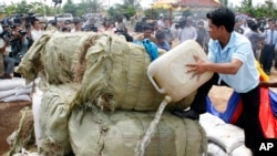 A Cambodian officer, right, pours fuel on to some three tons of various drugs, which were seized in raids earlier this year in eastern and southern Cambodia, on the outskirt of Phnom Penh, Cambodia, file photo.