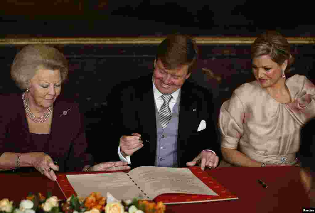 Queen Beatrix (L) of the Netherlands passes the act of abdication to her son Crown Prince Willem-Alexander next to his wife Crown Princess Maxima (R) during a ceremony at the Royal Palace in Amsterdam.