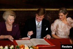 FILE - Queen Beatrix (L) of the Netherlands passes the act of abdication to her son Crown Prince Willem-Alexander next to his wife Crown Princess Maxima (R) during a ceremony at the Royal Palace in Amsterdam, April 30, 2013.