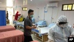 Tim polisi mengenakan APD memeriksa rumah sakit yang dilengkapi dengan tujuh tempat tidur di samping toko obat di Clark Freeport dan Zona Ekonomi Khusus barat laut Manila, 19 Mei 2020. (CIDG Regional Field Units 3 via AP)