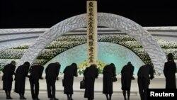 Keluarga korban bencana gempa bumi dan tsunami memberi hormat ke hadapan altar bertabur bunga chrysanthemums dalam peringatan tiga tahun bencana nasional tersebut di Tokyo (11/3).