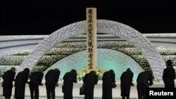 在日本大地震/海啸三周年之际,死难者亲属在一处祭坛前鞠躬,哀悼亲人。(2014年3月11日)