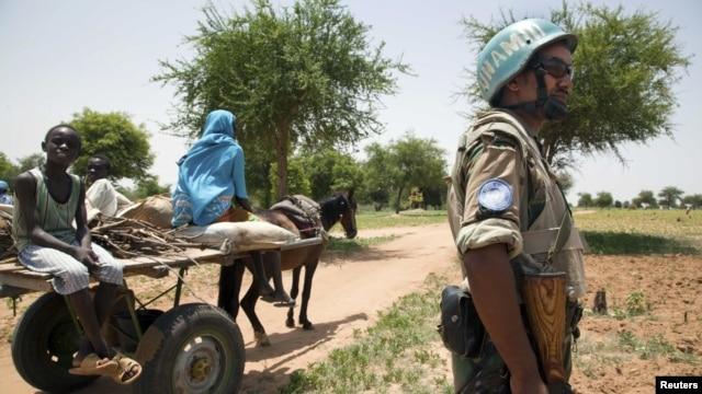 UNAMID peacekeeper Sergent Kindu Tarekegn, from Adigrat, Ethiopia, escorts a family that is returning home after farming outside Gereida, South Darfur, July 25, 2012.