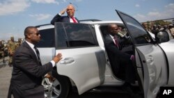 Haiti's outgoing President Michel Martelly delivers a goodbye salute to supporters before tucking into his vehicle outside the parliament building in Port-au-Prince, Haiti, Sunday, Feb. 7, 2016.