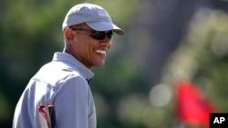 Le président Barack Obama, souriant, joue du golf, 12 aout 2015