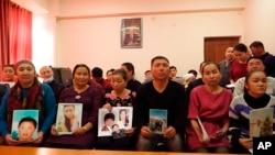 在哈薩克斯坦阿拉木圖一個中國哈薩克族人組織的辦公室裡,人們手舉在新疆失踪親屬的照片。 (2018年12月7日)