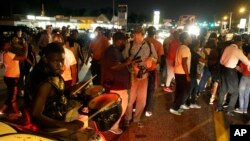 FILE - Protesters gather along West Florissant Avenue during demonstration in Ferguson, Missouri, Aug. 11, 2015.