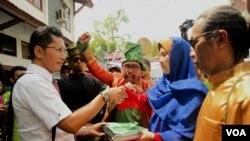 Indra Jaya, koordinator tim kuasa hukum menyerahkan berkas gugatan ke Pengadilan Negeri Pekanbaru, Riau, didampingi para aktivis selaku penggugat, Senin (14/3).