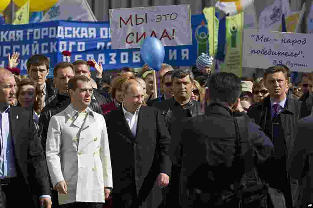 Russian President Dmitry Medvedev, 2nd left, and president-elect Vladimir Putin, 3rd left, take part in a May Day rally, organized by trade unions and United Russia party, in Moscow, Russia, May 1, 2012. (AP Photo)