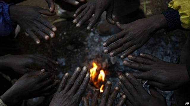 African migrants, displaced by anti-foreigner violence in Johannesburg, warm their hands around a small fire, May 2008 (file photo).