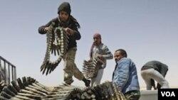 Pasukan pemberontak menyiapkan amunisi senjata di pinggiran kota Ajdabiya, Libya, Sabtu (16/4).