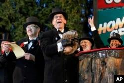 Groundhog Club handler Ron Ploucha, center, holds Punxsutawney Phil, the weather prognosticating groundhog, during the 129th celebration of Groundhog Day on Gobbler's Knob in Punxsutawney, PA., Feb. 2, 2015.