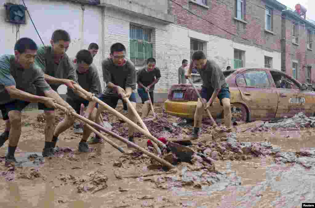Chinese People's Liberation Army soldiers clear mud from a street in a flood-hit area in Hougoumen village of Fangshan district in Beijing, July 25, 2012.